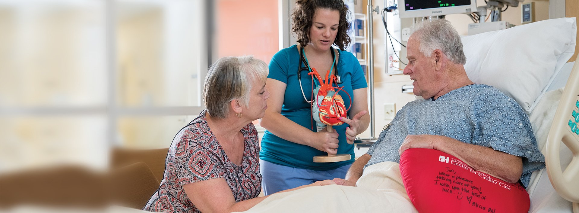 Nurse navigator and cardiac patient at the bedside