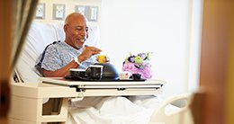 Patient  in bed with meal tray